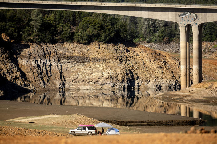 A family camps on a dry riverbed at Shasta Lake on Monday, May 24, 2021, in Shasta Trinity National Forest, Calif. At the time of this photo, the reservoir was at 45 percent of capacity and 52 percent of its historical average. (AP Photo/Noah Berger)