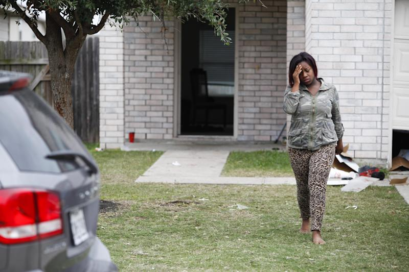 An unidentified woman walks away from the home Sunday, Nov. 10, 2013 where two people were killed and at least 20 others injured late Saturday when gunfire erupted at a house party in the Cypress area, authorities said. The shooting broke out about 11:15 p.m. in the 7300 block of Enchanted Creek Drive, in Houston. (AP Photo/Houston Chronicle, Eric Kayne)