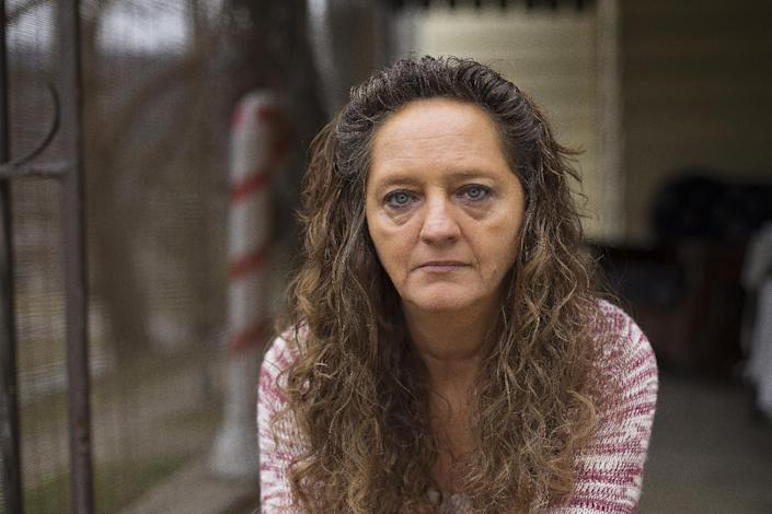 In this Monday, Dec. 19, 2016, photo, Donna Dye, who is unemployed and whose husband is disabled, sits outside her home in Minnie, Ky. She and her husband have been fighting the federal government to keep his Social Security disability checks after a local lawyer who helped them became the subject of a federal fraud investigation. (AP Photo/David Stephenson)
