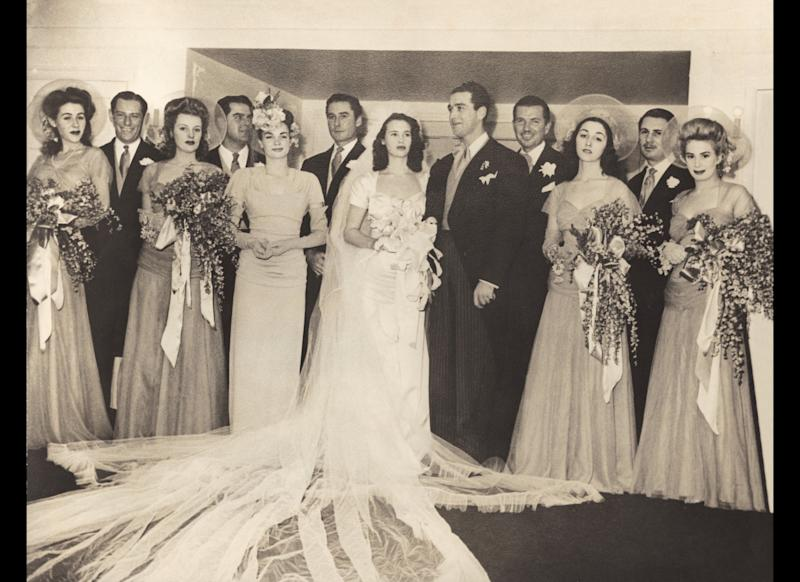 "Gloria's wedding to Pasquale ""Pat"" De Cicco on December 28, 1941, in Santa Barbara, California. The ceremony lasted four hours. Gloria's mother sold her father's champion horse trophies to help pay for the marriage and planned it to the last detail. ""It was a nightmare,"" remembers Gloria. Members of the wedding party included Betsy Bloomingdale on the far left, Errol Flynn to the left of Gloria, and Carol Marcus at the far right."