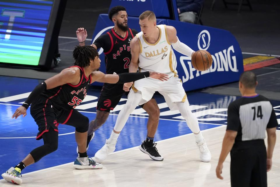 Toronto Raptors' Freddie Gillespie (55) and Jalen Harris (2) defend as Dallas Mavericks' Kristaps Porzingis (6) works to the basket in the second half of an NBA basketball game in Dallas, Friday, May 14, 2021. Referee Curtis Blair (74) looks on at the play. (AP Photo/Tony Gutierrez)