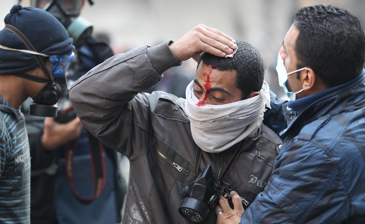 CAIRO, EGYPT - NOVEMBER 23:  An injured protestor  is led away during clashes with police near Tahrir Square on November 23, 2011 in Cairo, Egypt. Thousands of Egyptians are continuing to occupy Tahrir Square after four days of clashes with security forces despite a promise from military leaders to bring forward Presidential elections.  (Photo by Peter Macdiarmid/Getty Images)