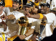 Los Angeles Lakers guard Derek Fisher, center, holds the Larry O'Brien Trophy as Kobe Bryant, right, holds the MVP trophy as they celebrate after beating the Boston Celtics, 83-79, in Game 7 of the NBA basketball finals in Los Angeles, June 17, 2010. At second left is Lakers' Sasha Vujacic. Bryant, the 18-time NBA All-Star who won five championships and became one of the greatest basketball players of his generation during a 20-year career with the Los Angeles Lakers, died in a helicopter crash Sunday, Jan. 26, 2020. (AP Photo/Mark J. Terrill)