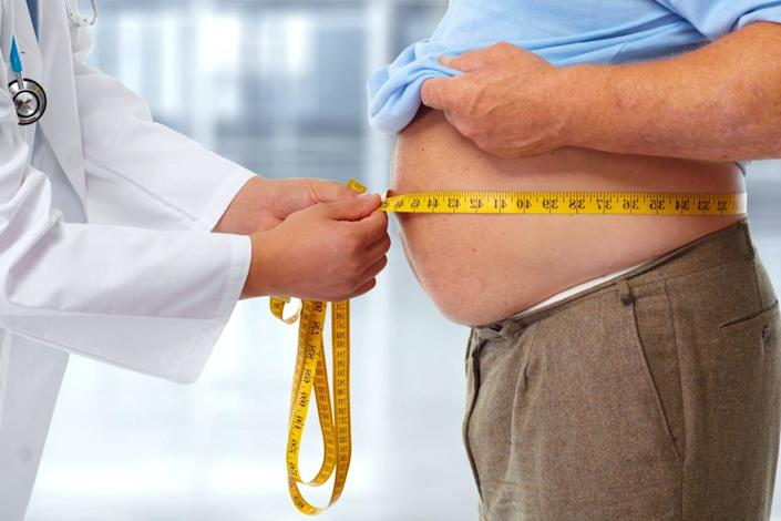 Doctor measuring obese man waist body fat. Obesity and weight loss