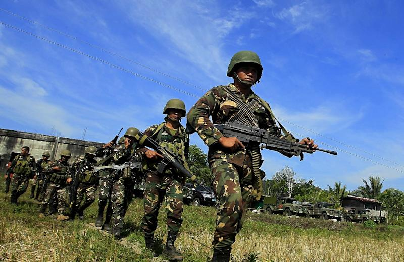 Philippine soldiers march on a rice field as they end an operation against Islamic Militants (AFP Photo/Mark Navales)