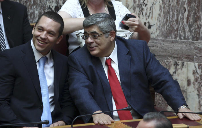FILE - In this June 28, 2012 file photo, extreme right Golden Dawn party leader Nikos Mihaloliakos, right, speaks with the party spokesman Ilias Kasidiaris during the swearing-in ceremony in Athens. Greek police said Mihaloliakos was arrested on Saturday, Sept. 28, 2013 on charges of forming a criminal organization. Warrants for the arrest of another five Golden Dawn parliament deputies have been issued. The police counterterrorism unit is looking for the deputies. More warrants are expected. (AP Photo/Thanassis Stavrakis, File)