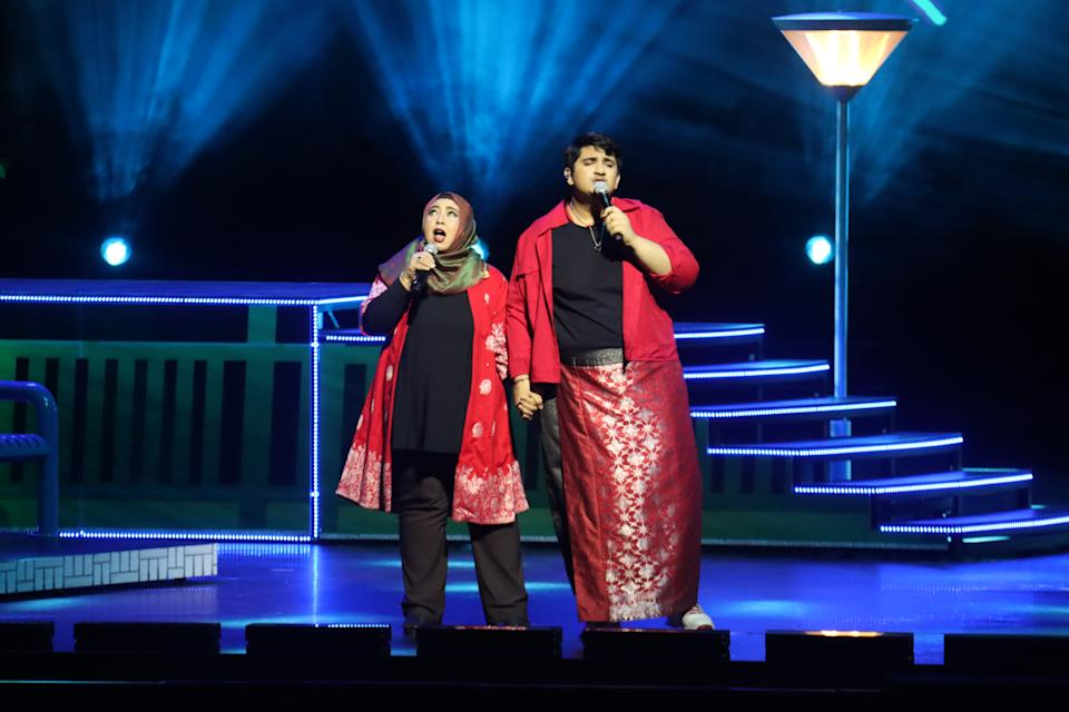 Local singer-songwriter Shazuan Shiraj, known as Abangsapau (right), performing his original song Each Other, with his mother Farhana binte Ibrahim, during a rehearsal for the National Day Parade 2020 Evening Show at the Star Performing Arts Centre. (Photo: NDP2020 Exco)