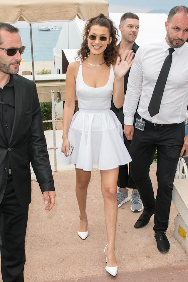 <p>Arriving in Cannes for the Magnum x Alexander Wang press conference, Bella Hadid wore the ultimate white summer dress, which she paired with slim sunnies and slingback heels. <br>(Photo: Getty) </p>