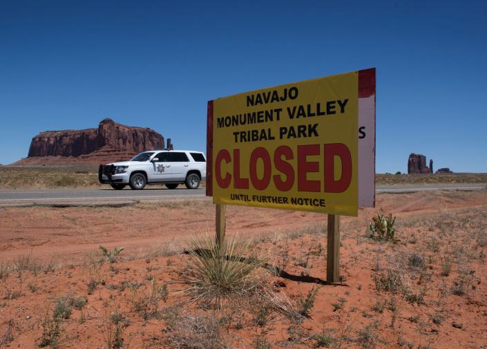 "<span class=""caption"">Monument Valley Tribal Park in Arizona, closed due to the pandemic. Normally, the park would be teeming with tourists this time of year.</span> <span class=""attribution""><a class=""link rapid-noclick-resp"" href=""https://www.gettyimages.com/detail/news-photo/navajo-park-ranger-drives-outside-the-navajo-nation-managed-news-photo/1214464353?adppopup=true"" rel=""nofollow noopener"" target=""_blank"" data-ylk=""slk:Getty Images / Mark Ralston"">Getty Images / Mark Ralston</a></span>"