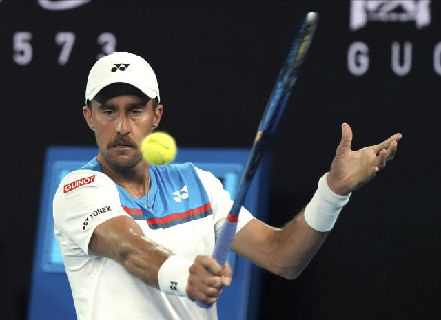 United States' Steve Johnson makes a backhand return to Switzerland's Roger Federer during their first round singles match at the Australian Open tennis championship in Melbourne, Australia, Monday, Jan. 20, 2020. (AP Photo/Lee Jin-man)