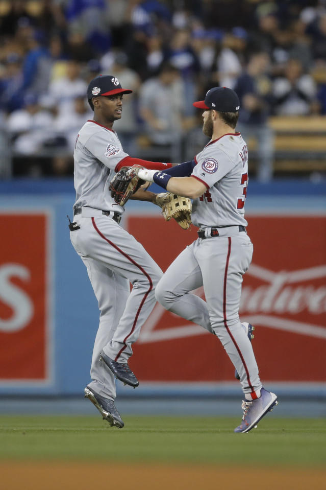 Washington Nationals' Michael Taylor, left, and Bryce Harper celebrate the team's 5-2 win over the Los Angeles Dodgers in a baseball game, Friday, April 20, 2018, in Los Angeles. (AP Photo/Jae C. Hong)