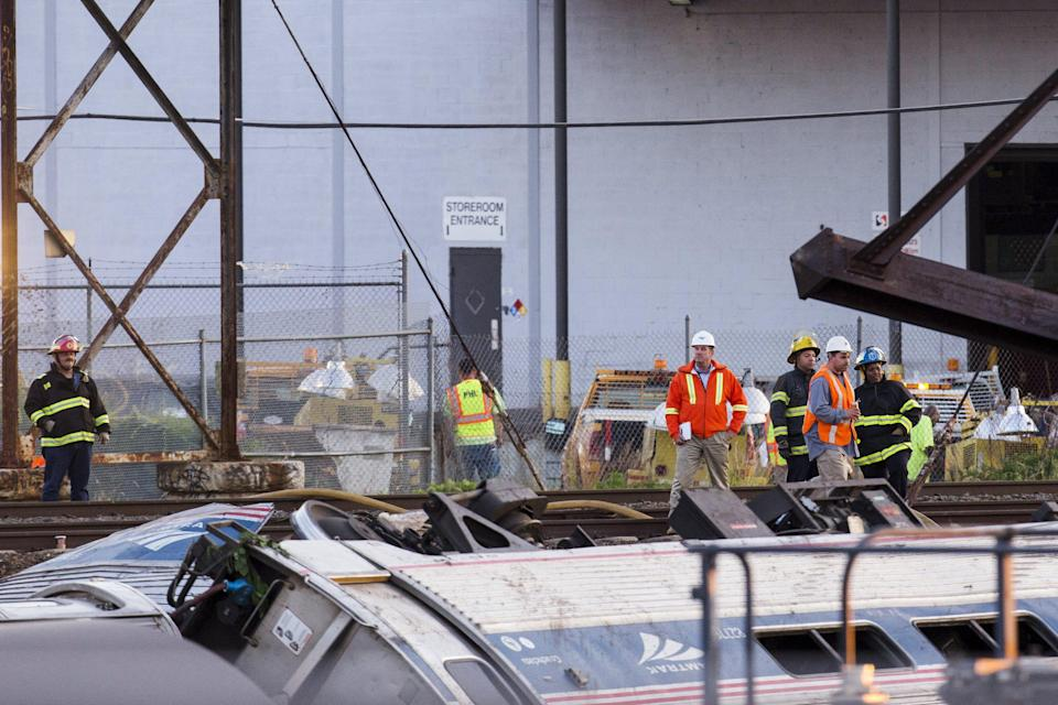 Emergency workers survey the remains of a derailed Amtrak train in Philadelphia, Pennsylvania May 13, 2015. An Amtrak passenger train with more than 200 passengers on board derailed in north Philadelphia on Tuesday night, killing at least five people and injuring more than 50 others, several of them critically, authorities said. Authorities said they had no idea what caused the train wreck, which left some demolished rail cars strewn upside down and on their sides in the city's Port Richmond neighborhood along the Delaware River. REUTERS/Lucas Jackson