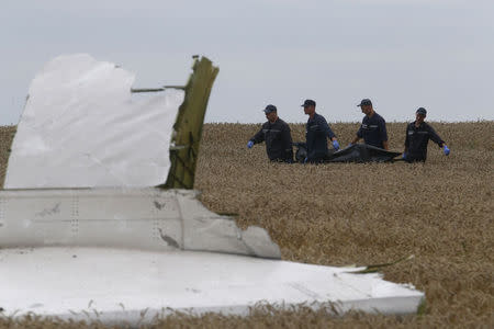Members of the Ukrainian Emergency Ministry carry a body at the crash site of Malaysia Airlines Flight MH17, near the settlement of Grabovo in the Donetsk region July 19, 2014. REUTERS/Maxim Zmeyev