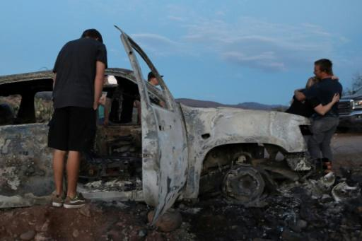 Members of the LeBaron family look at a car that was fired upon and burned during an ambush in Bavispe, Sonora mountains, Mexico, on November 5, 2019