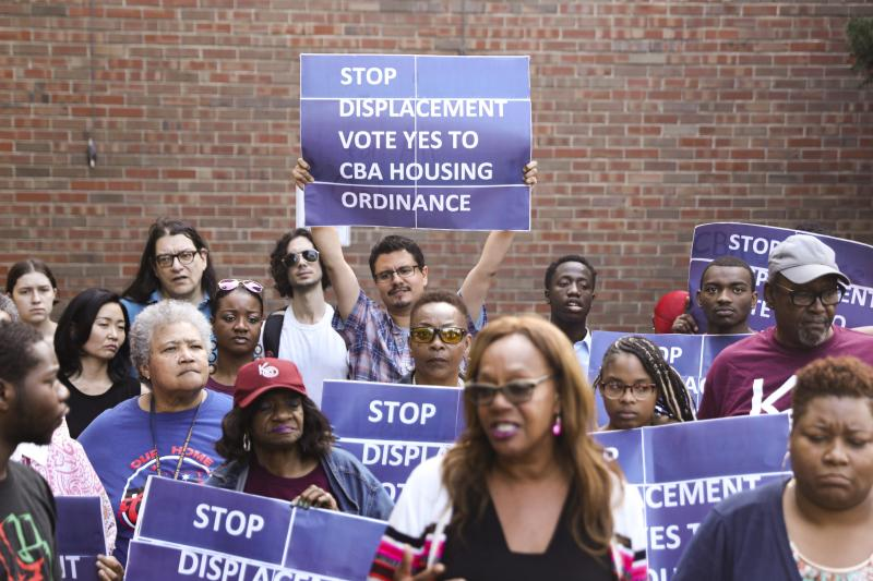 In this Tuesday, July 23, 2019 photo, activist Jose Reuena, center in back row, holds a placard during a news conference and rally in Chicago. (AP Photo/Amr Alfiky)