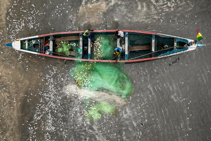 An aerial shot of a Gambian fishing boat with Gambian fishermen. (Fábio Nascimento / The Outlaw Ocean Project)