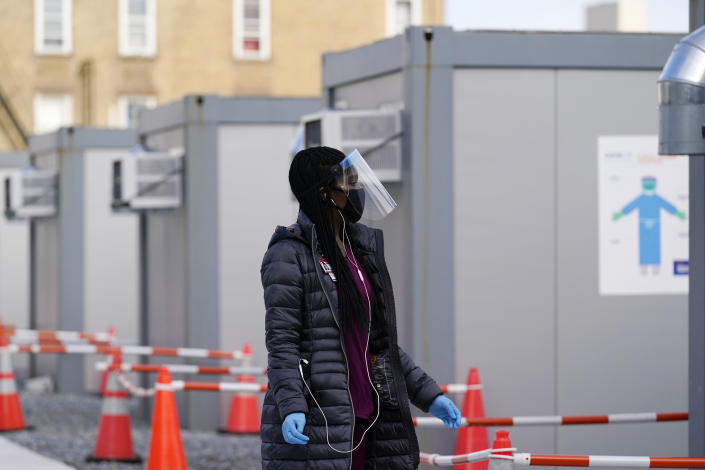 A worker wear a protective face shield walks between portable units set up for registration and testing at a New York City Health + Hospitals COVID-19 testing site in the Brooklyn borough of New York, Thursday, Nov. 19, 2020. (AP Photo/Kathy Willens)