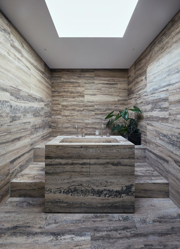 """<div class=""""caption""""> One of the bathrooms is covered entirely in silver travertine, including the custom basin. </div>"""