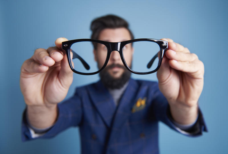 Man holding eyeglasses in front his face