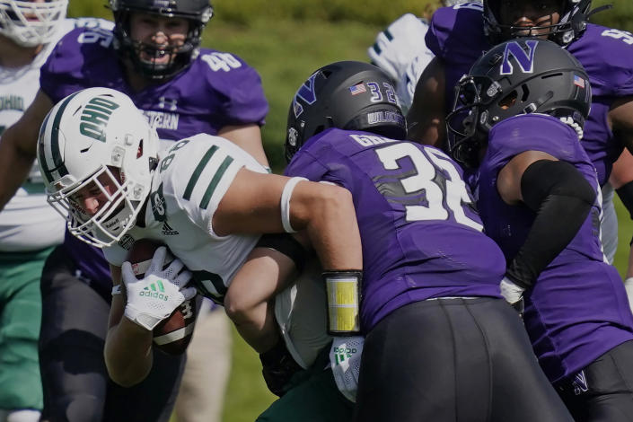 Ohio tight end Ryan Luehrman, left, is tackled by Northwestern linebacker Bryce Gallagher, center, and safety Brandon Joseph during the first half of an NCAA college football game in Evanston, Ill., Saturday, Sept. 25, 2021. (AP Photo/Nam Y. Huh)