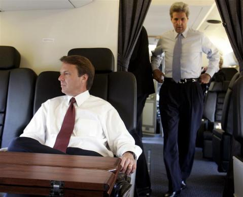 Then Vice Presidential candidate John Edwards (L) sits on the campaign plane as running mate, then presidential candidate Senator John Kerry, enters the cabin in New York City, July 8, 2004.