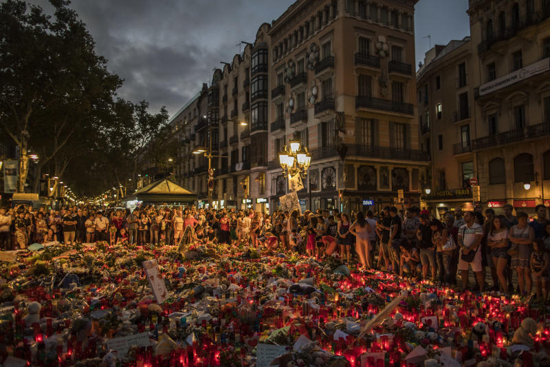 People stand next to candles and flowers placed on the ground, after a terror attack that left many killed and wounded in Barcelona, Spain, Monday, Aug. 21, 2017. The lone fugitive from the Spanish cell that killed 15 people in and near Barcelona was shot to death Monday after he flashed what turned out to be a fake suicide belt at two troopers who confronted him in a vineyard just outside the city he terrorized, authorities said. (AP Photo/Santi Palacios)