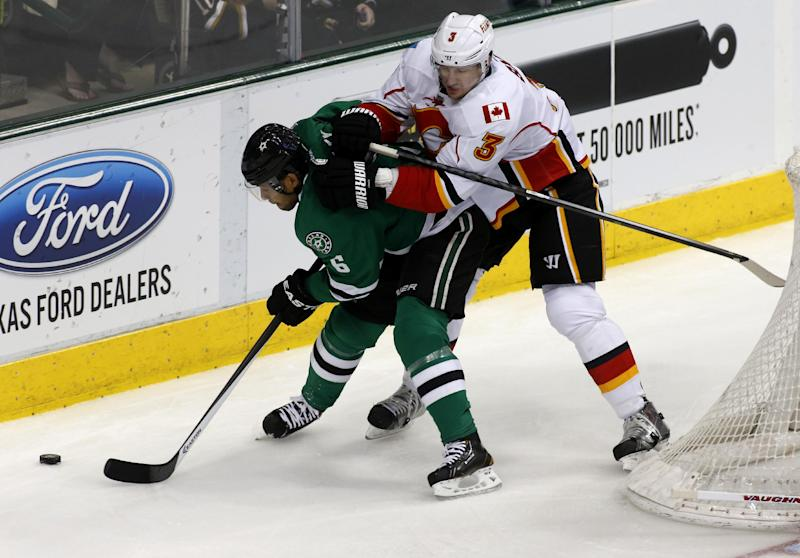 Dallas Stars defenseman Trevor Daley (6) and Calgary Flames defenseman Ladislav Smid (3), of Russia, fight for the puck in the first period of an NHL hockey game Friday, March 14, 2014, in Dallas. (AP Photo/Sharon Ellman)