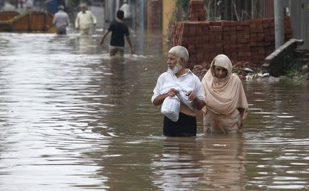 A couple wades through a flooded road after heavy rains in Lahore September 4, 2014. REUTERS/Mohsin Raza