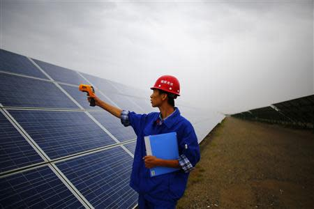 A worker inspects solar panels at a solar farm in Dunhuang, 950km (590 miles) northwest of Lanzhou, Gansu Province September 16, 2013. REUTERS/Carlos Barria