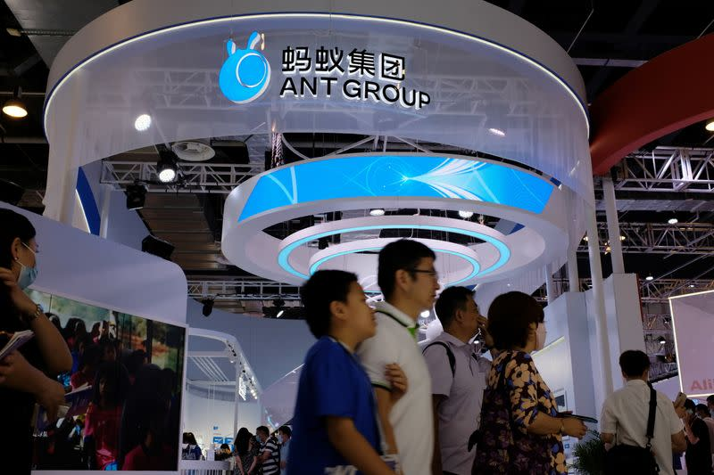 People walk past the Ant Group booth in Shanghai