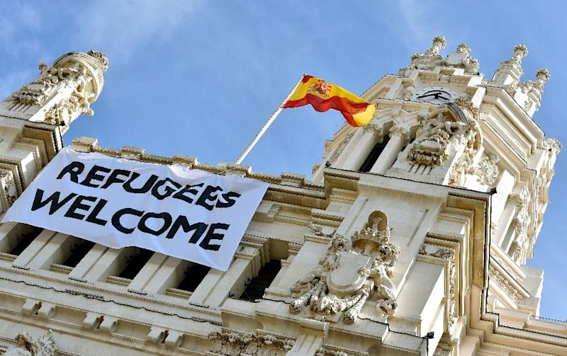 """A Spanish flag flies above a banner reading """"Refugees Welcome"""" hanging on the facade of the Cibeles Palace, the Madrid City Hall, on September 7, 2015 (AFP Photo/Gerard Julien)"""