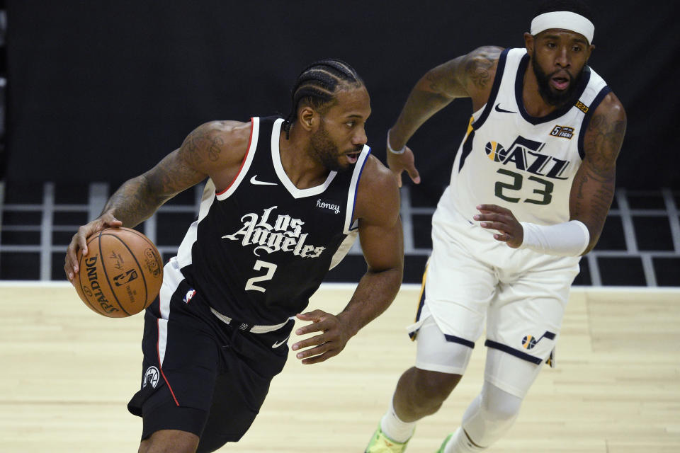 Los Angeles Clippers forward Kawhi Leonard, left, is defended by Utah Jazz forward Royce O'Neale during the first half of an NBA basketball game in Los Angeles, Friday, Feb. 19, 2021. (AP Photo/Kelvin Kuo)