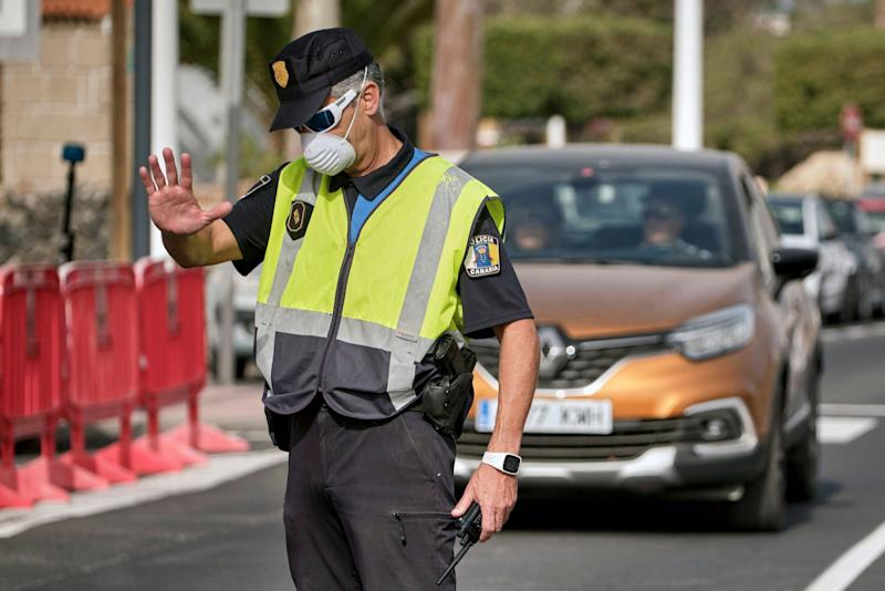 A police officer controls the road to the H10 Costa Adeje Palace hotel in Tenerife, Canary Island, Spain, Tuesday, Feb. 25, 2020. Spanish officials say a tourist hotel on the Canary Islands has been placed in quarantine after an Italian doctor staying there tested positive for the new coronavirus. (AP Photo) (Photo: ASSOCIATED PRESS)
