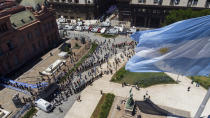 People line up outside the presidential palace alongside Plaza de Mayo, to pay final respects to Diego Maradona, in Buenos Aires, Argentina, Thursday, Nov. 26, 2020. The Argentine soccer great who led his country to the 1986 World Cup title died Wednesday at the age of 60. (AP Photo/Mario De Fina)