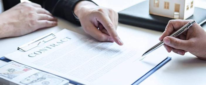 Estate agent broker pointing contract form to client signing agreement