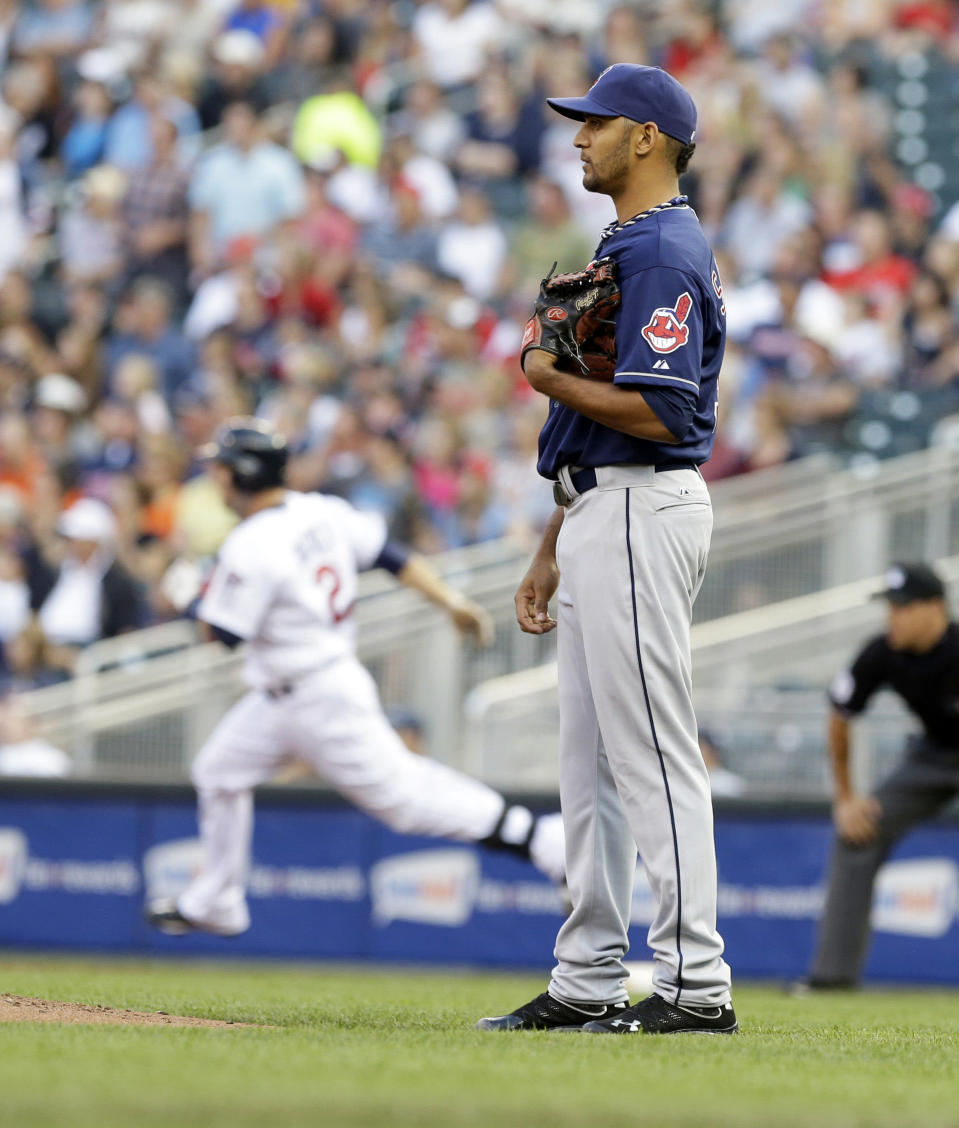 Cleveland Indians pitcher Danny Salazar, right, waiits for the ball after giving up a solo home run to Minnesota Twins' Brian Dozier, background, in the first inning of a baseball game, Monday, Aug. 12, 2013 in Minneapolis. (AP Photo/Jim Mone)