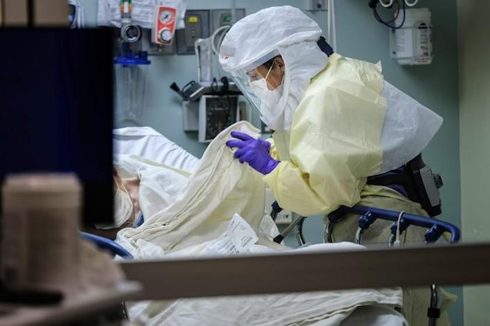 "Wearing personal protective equipment, registered nurse April Bandi cares for a patient in a special negative pressure isolation room at Sharp Memorial Hospital in San Diego on April 10. <span class=""copyright"">(Marcus Yam / Los Angeles Times)</span>"