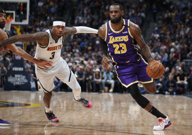 Los Angeles Lakers forward LeBron James, right, drives to the rim past Denver Nuggets forward Torrey Craig during the first half of an NBA basketball game Wednesday, Feb. 12, 2020, in Denver. (AP Photo/David Zalubowski)