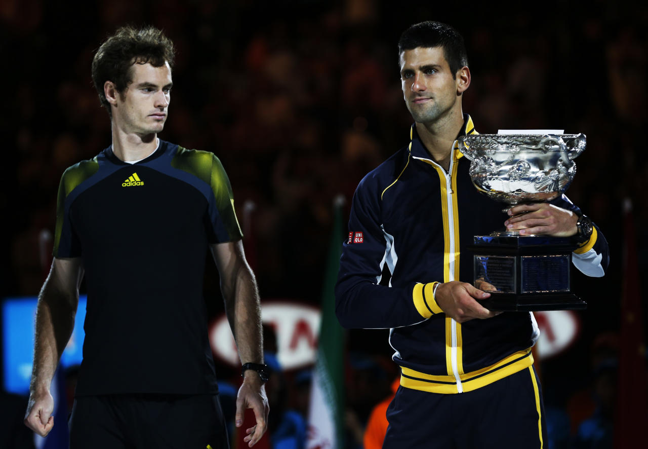 Runner-up Andy Murray of Britain (L) looks on as Novak Djokovic of Serbia poses with the Norman Brookes Challenge Cup after their men's singles final match at the Australian Open tennis tournament in Melbourne January 27, 2013.  REUTERS/Damir Sagolj (AUSTRALIA  - Tags: SPORT TENNIS)   - RTR3D18Y