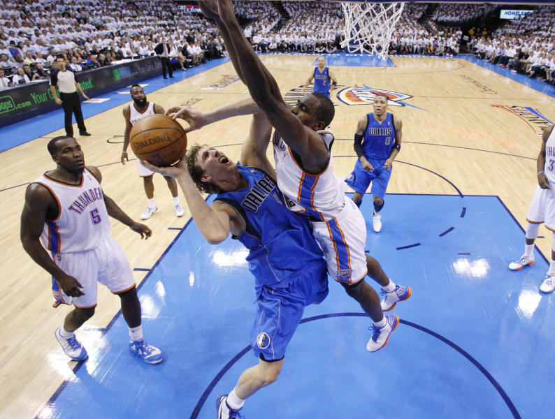 Dallas Mavericksforward Dirk Nowitzki, center, shoots as Oklahoma City Thunder forward Serge Ibaka , right, defends, in the second quarter of Game 2 in the first round of the NBA basketball playoffs, in Oklahoma City, Monday, April 30, 2012. (AP Photo/Sue Ogrocki)