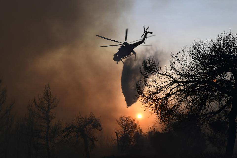 An helicopter drops water over a wildfire in Kryoneri area, northern Athens, Greece, Thursday, Aug. 5, 2021. Wildfires rekindled outside Athens and forced more evacuations around southern Greece Thursday as weather conditions worsened and firefighters in a round-the-clock battle stopped the flames just outside the birthplace of the ancient Olympics. (AP Photo/Michael Varaklas)