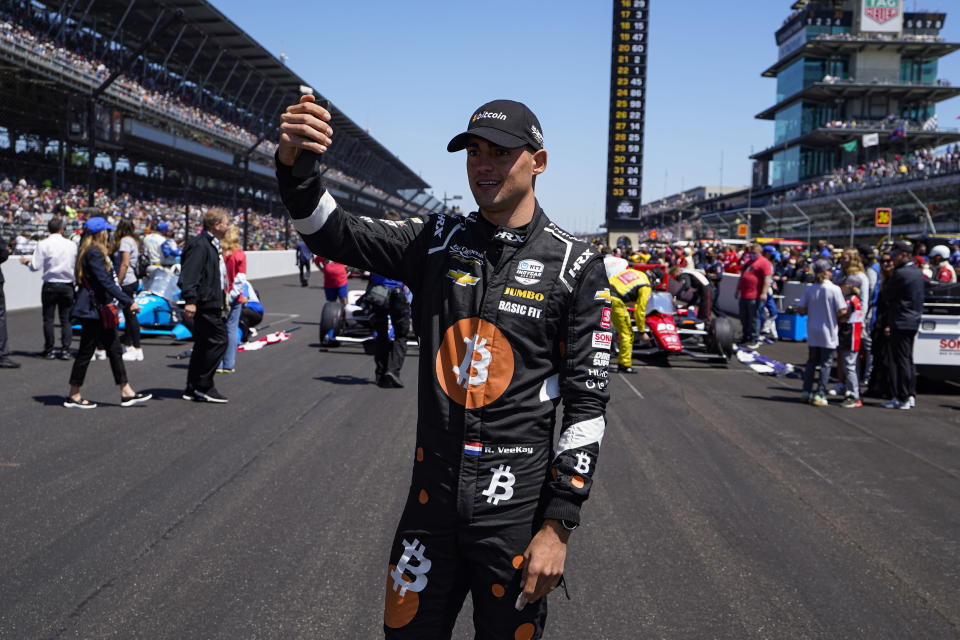 Rinus VeeKay, of the Netherlands, takes a photo as he walks to his car on the grid before the Indianapolis 500 auto race at Indianapolis Motor Speedway in Indianapolis, Sunday, May 30, 2021. (AP Photo/Michael Conroy)