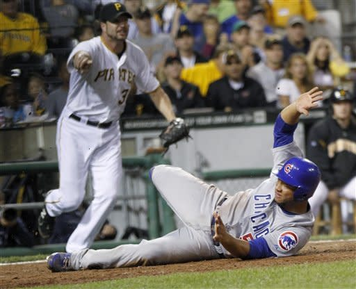 Pittsburgh Pirates relief pitcher Jason Grilli, left, watches as Chicago Cubs' Welington Castillo rolls after he scored on a hit by David DeJesus in the eighth inning of a baseball game Saturday, Sept. 8, 2012, in Pittsburgh. (AP Photo/Keith Srakocic)