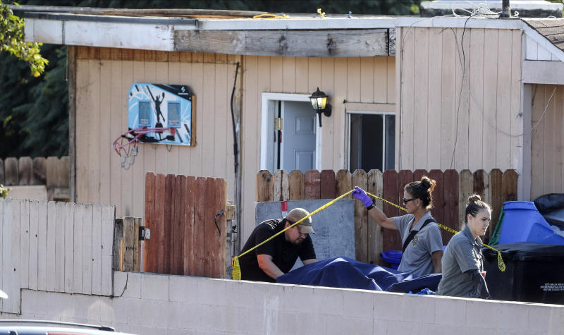 A body is carried out on a gurney at the home where two adults and three children died from gunshot wounds during a domestic shooting in the Paradise Hills area in San Diego, Calif., Saturday, Nov. 16, 2019. A husband and wife and three of their young children died Saturday morning at the family's San Diego home in what police believe was a murder-suicide sparked by a bitter divorce. One son is in critical condition. (Hayne Palmour IV/The San Diego Union-Tribune via AP)