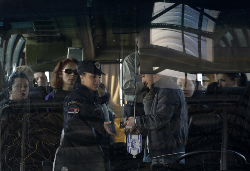 In this Oct. 22, 2012 photo a Serbian border police officer, left, checks the identification of passengers as the transit bus is crossing from Macedonia to the Serbia, at the Presevo border crossing, 380 kms south of Belgrade, Serbia. While about 99 percent of the asylum requests coming from the citizens of the Balkan nations have been rejected as unfounded, the influx has burdened the system of some EU nations, where the numbers of asylum seekers have increased ten-fold since the travel visas were abolished for much of the region in 2009. (AP Photo/Darko Vojinovic)