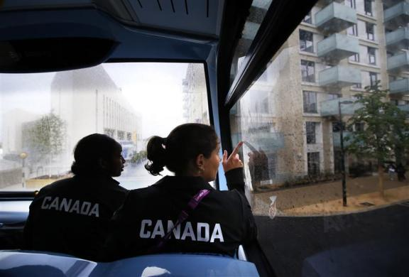Canadian women's soccer team players Robyn Gayle (L) and Rhian Wilkinson look out the window from a double-decker bus as they arrive at the Athletes' Village at the Olympic Park in London July 18, 2012.