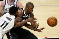 Brooklyn Nets guard Kyrie Irving, left, and Los Angeles Clippers center Serge Ibaka go after a rebound during the first half of an NBA basketball game Sunday, Feb. 21, 2021, in Los Angeles. (AP Photo/Mark J. Terrill)