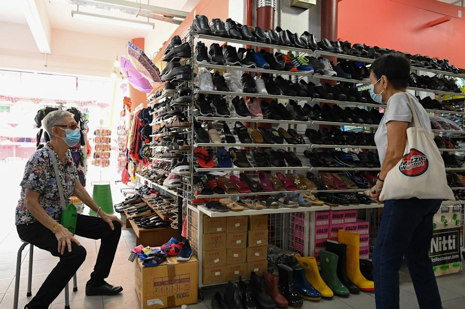 """A woman browses through footwear on sale at a stall in Singapore on June 19, 2020, as retail shops reopen due to the easing of restrictions to prevent the spread of the COVID-19 novel coronavirus. - Restaurants, retail shops and most other businesses reopened in Singapore on June 19 as the virus-hit city-state eased curbs, but the city-state's leader cautioned residents """"not to go overboard celebrating"""". (Photo by Roslan RAHMAN / AFP) (Photo by ROSLAN RAHMAN/AFP via Getty Images)"""