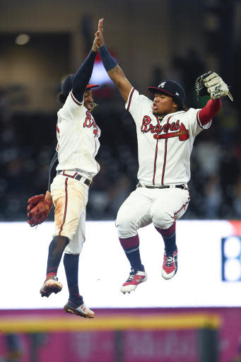 Atlanta Braves' Ozzie Albies and Ronald Acuna Jr., right, celebrate after the team's baseball game against the New York Mets, Wednesday, Aug.14, 2019, in Atlanta. The Braves won 6-4. (AP Photo/John Amis)