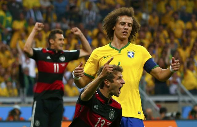 Germany's Thomas Mueller celebrates after scoring a goal, as Brazil's David Luiz watches, during their 2014 World Cup semi-finals at the Mineirao stadium in Belo Horizonte July 8, 2014. REUTERS/Eddie Keogh (BRAZIL - Tags: TPX IMAGES OF THE DAY SOCCER SPORT WORLD CUP)